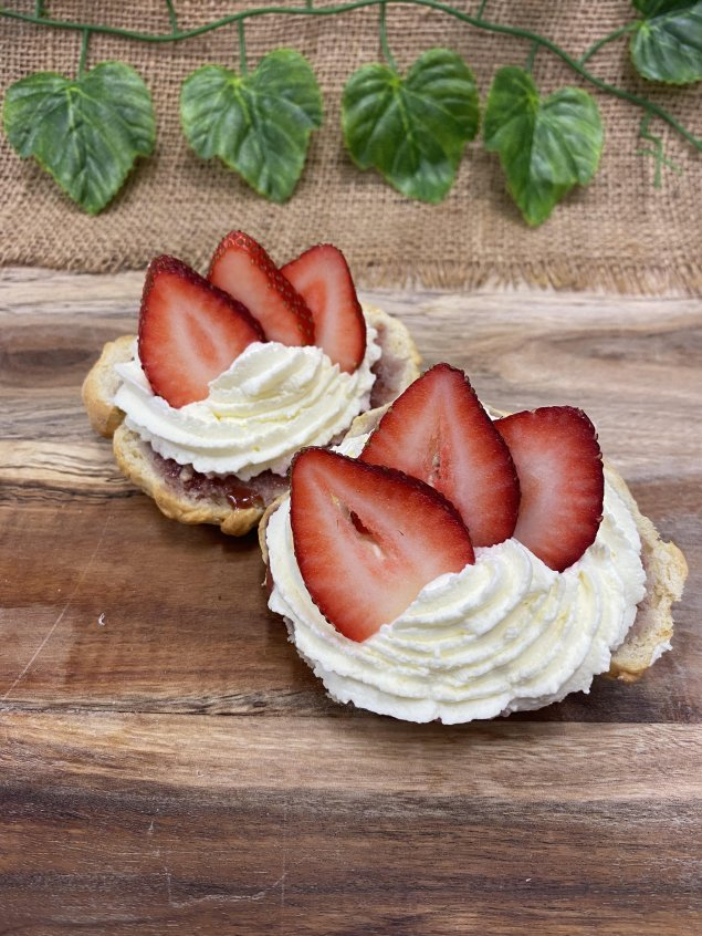 Sweet scone halves topped with jam, whipped cream, and strawberries (v)